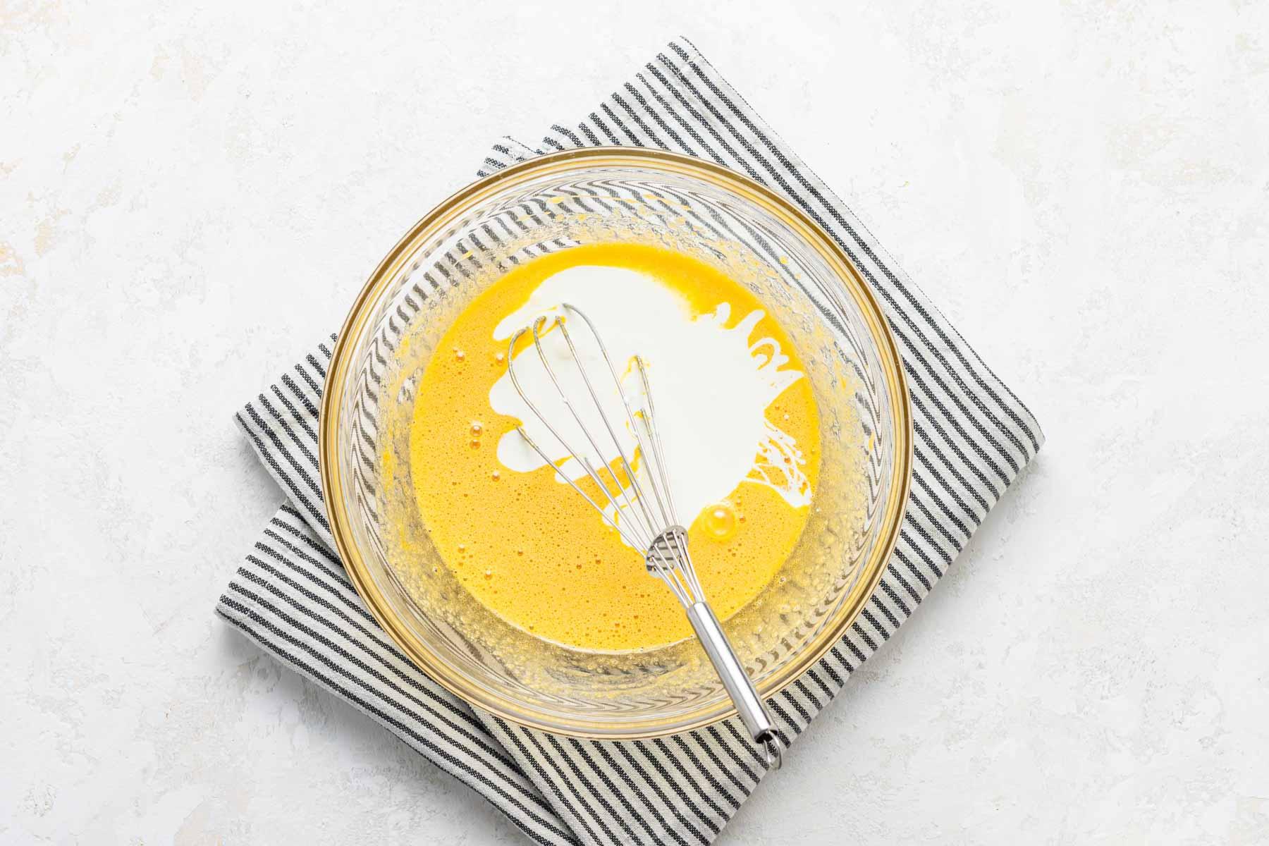 Heavy cream in egg yolk mixture in glass bowl.