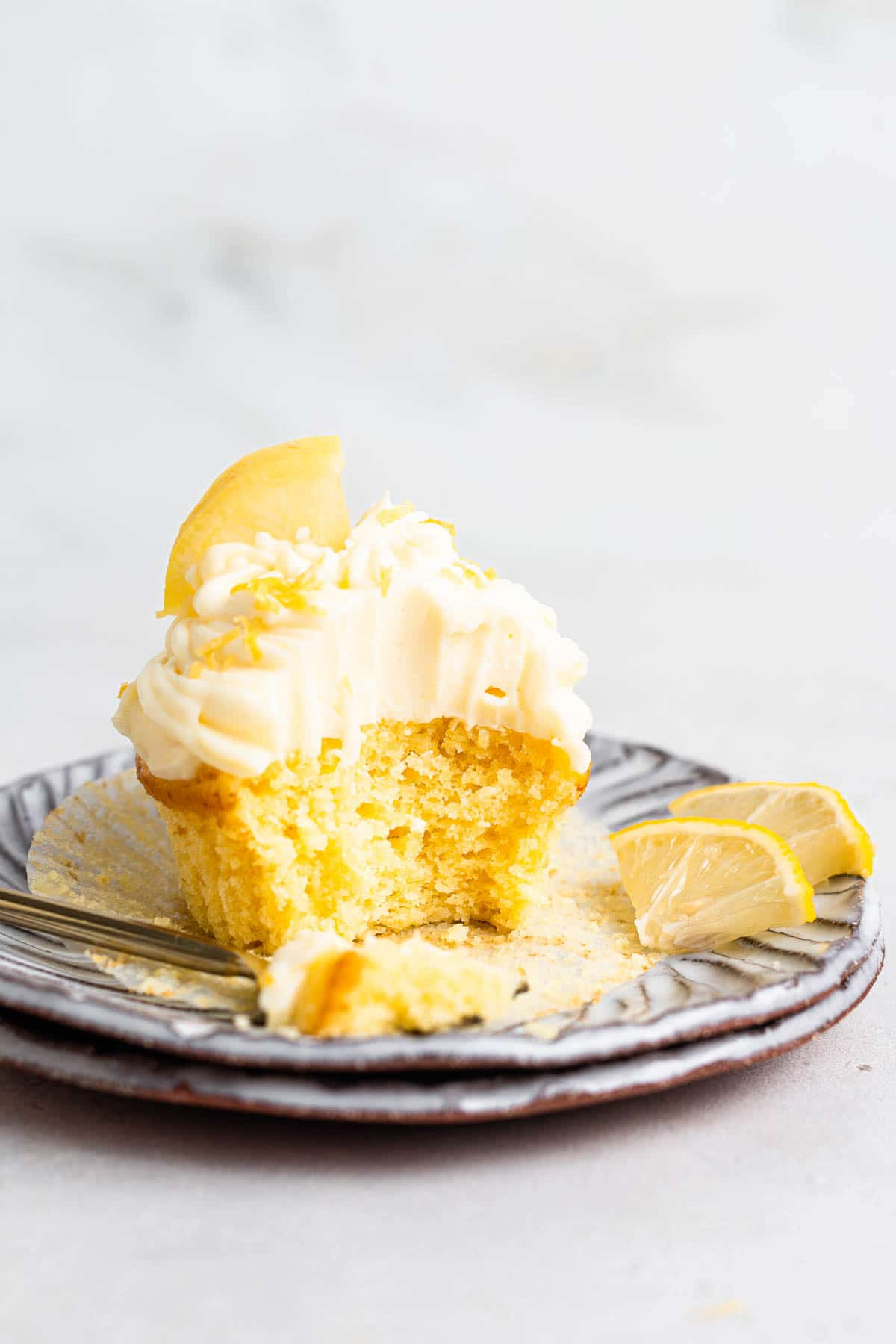 Single lemon cupcake with lemon cream cheese frosting on a plate.