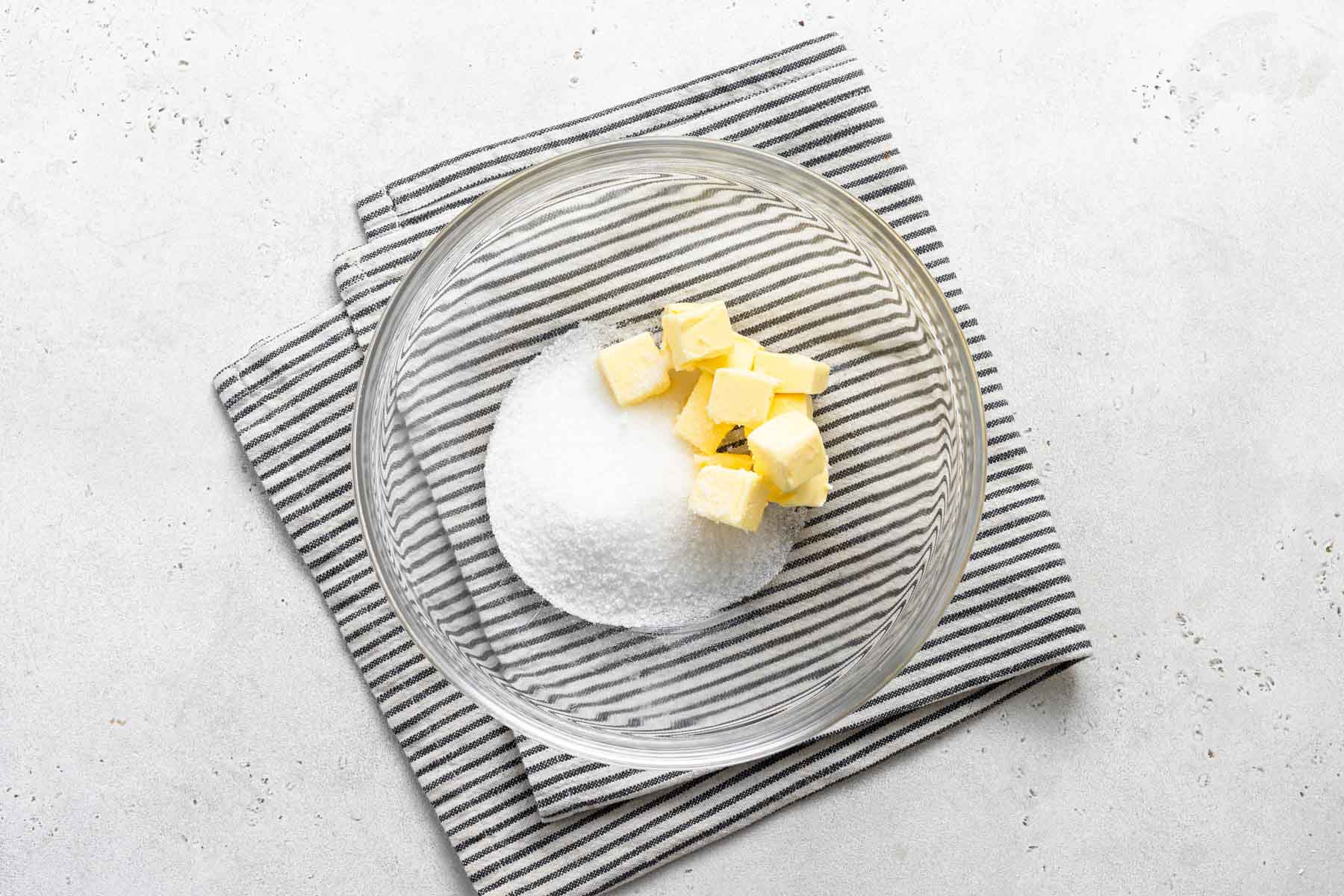 Diced butter and granulated sugar in clear glass bowl.