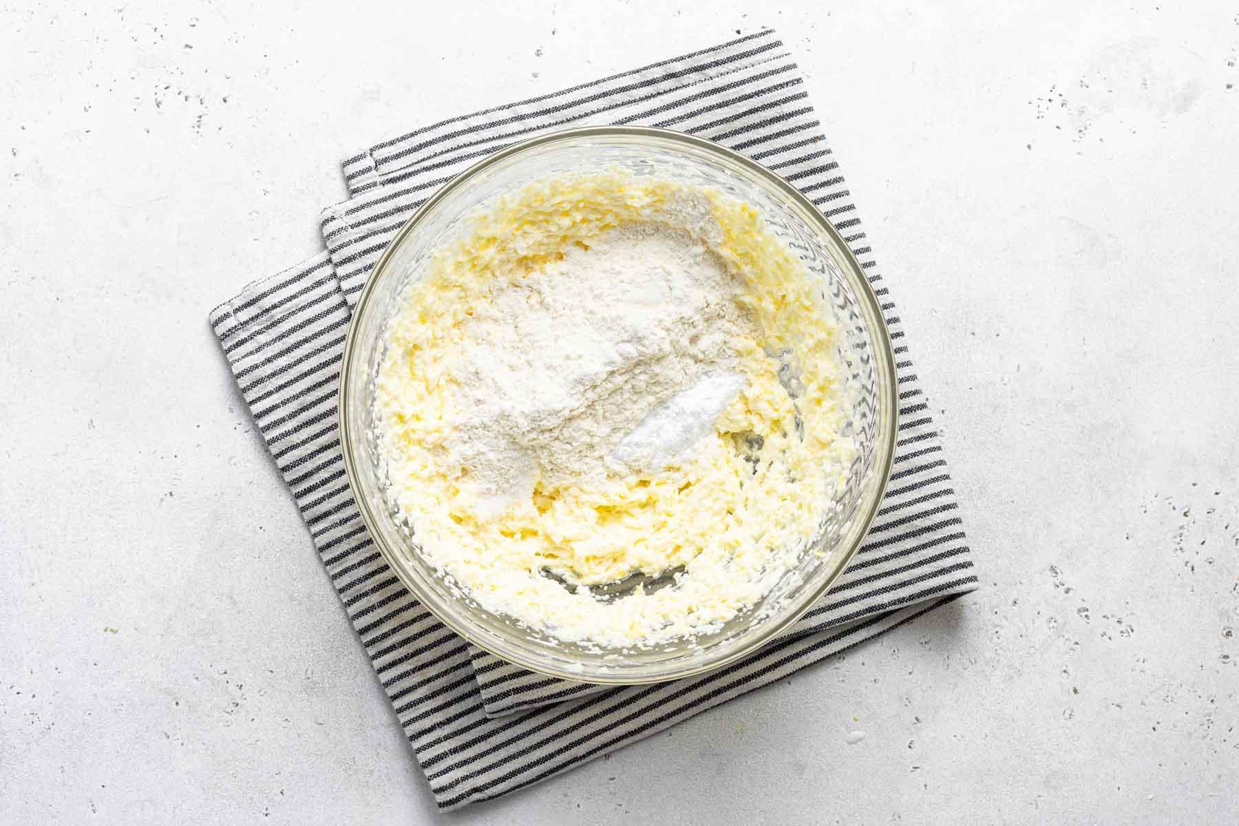 Lemon cupcake batter in bowl with dish towel.