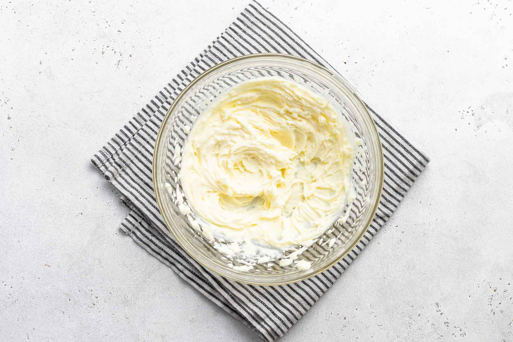 Lemon cream cheese frosting in clear bowl.