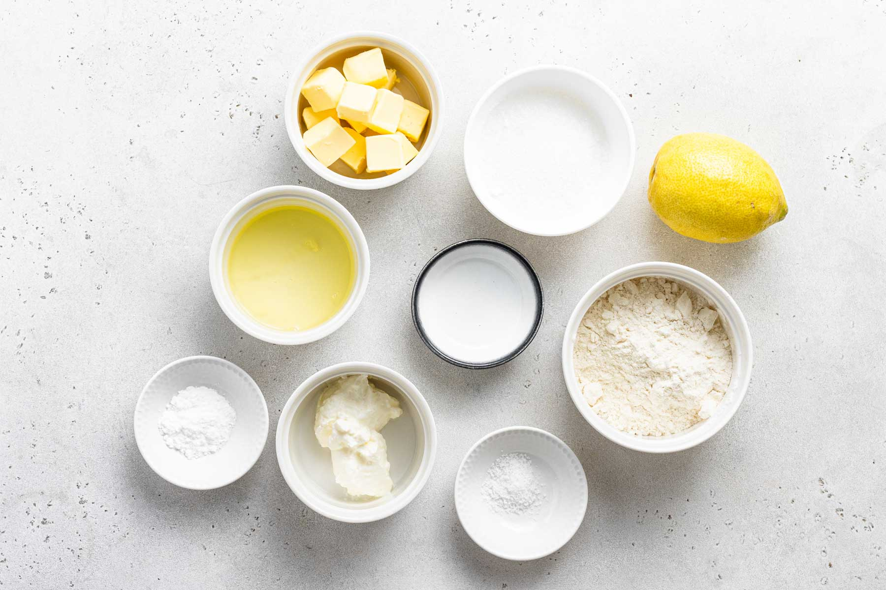 Ingredients for lemon cupcakes measured in white bowls.