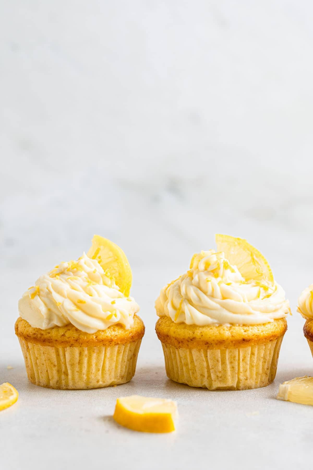 Two lemon cupcakes with fresh lemon slices.
