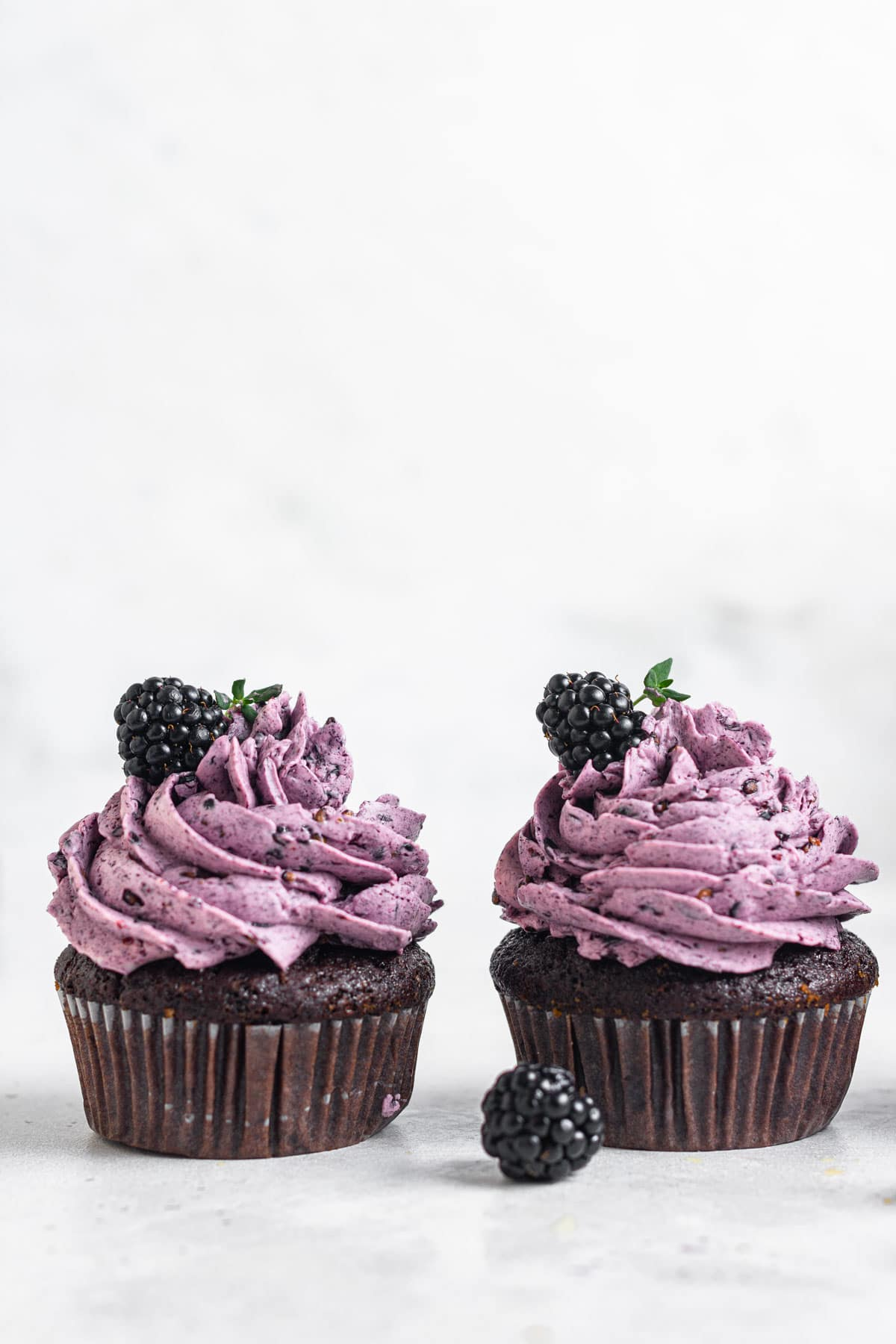Two chocolate cupcakes with purple frosting and fresh blackberries.