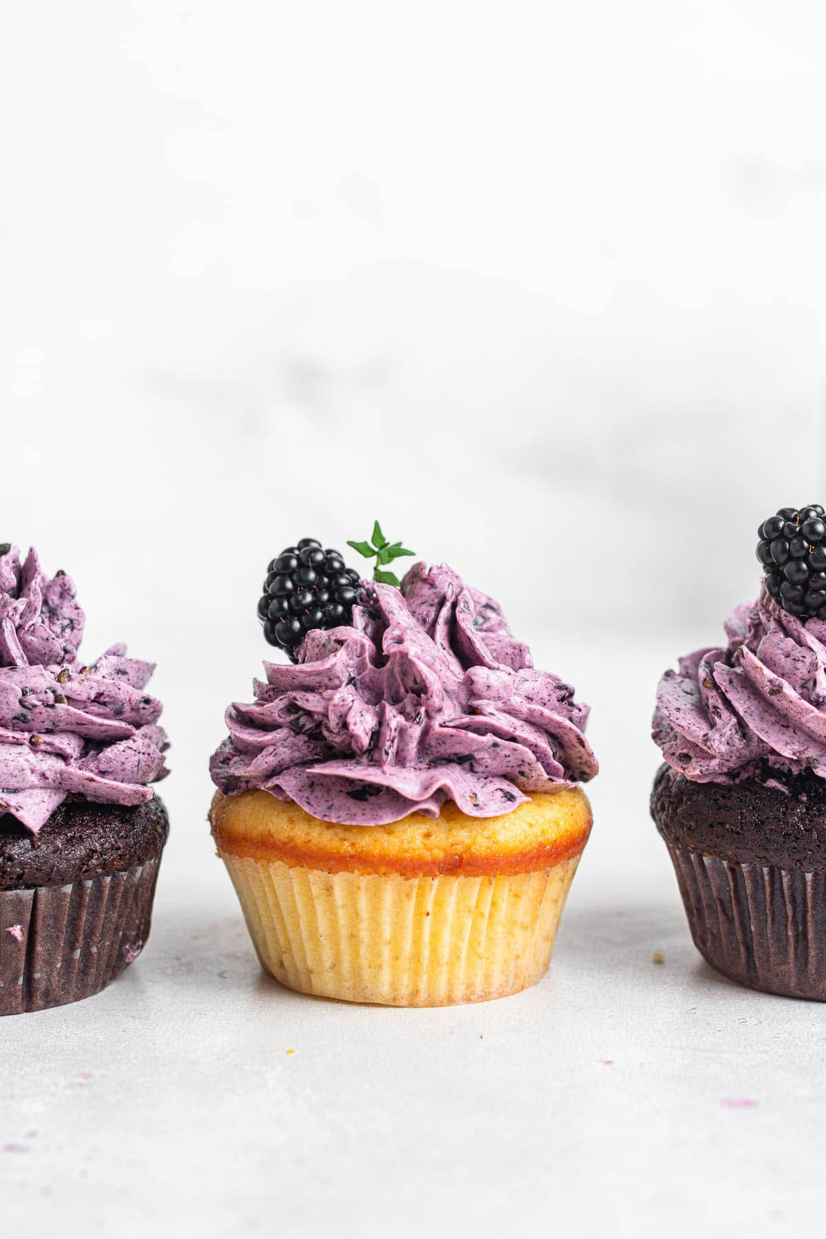 Three cupcakes with purple frosting.