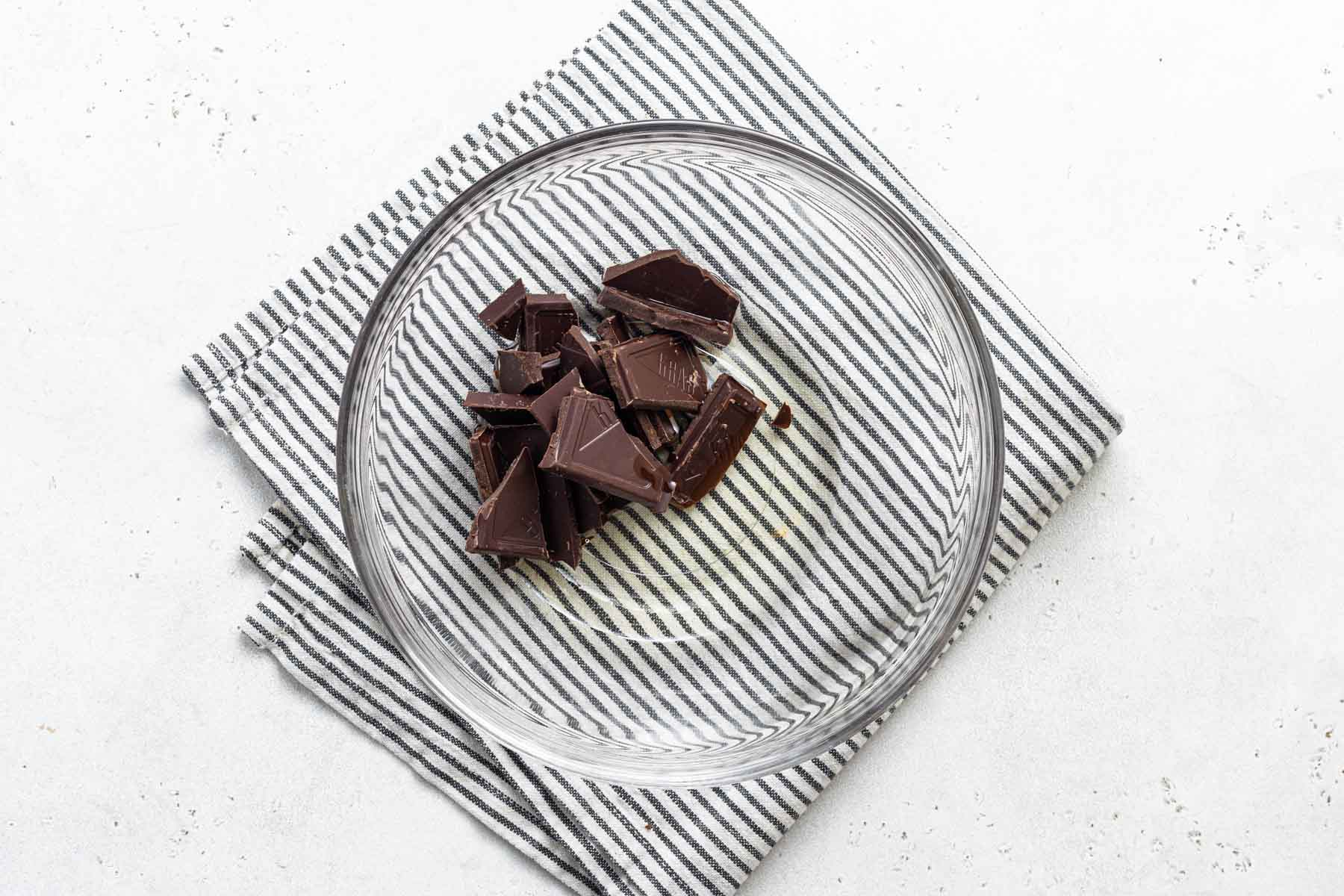 Chopped chocolate and oil in glass bowl.