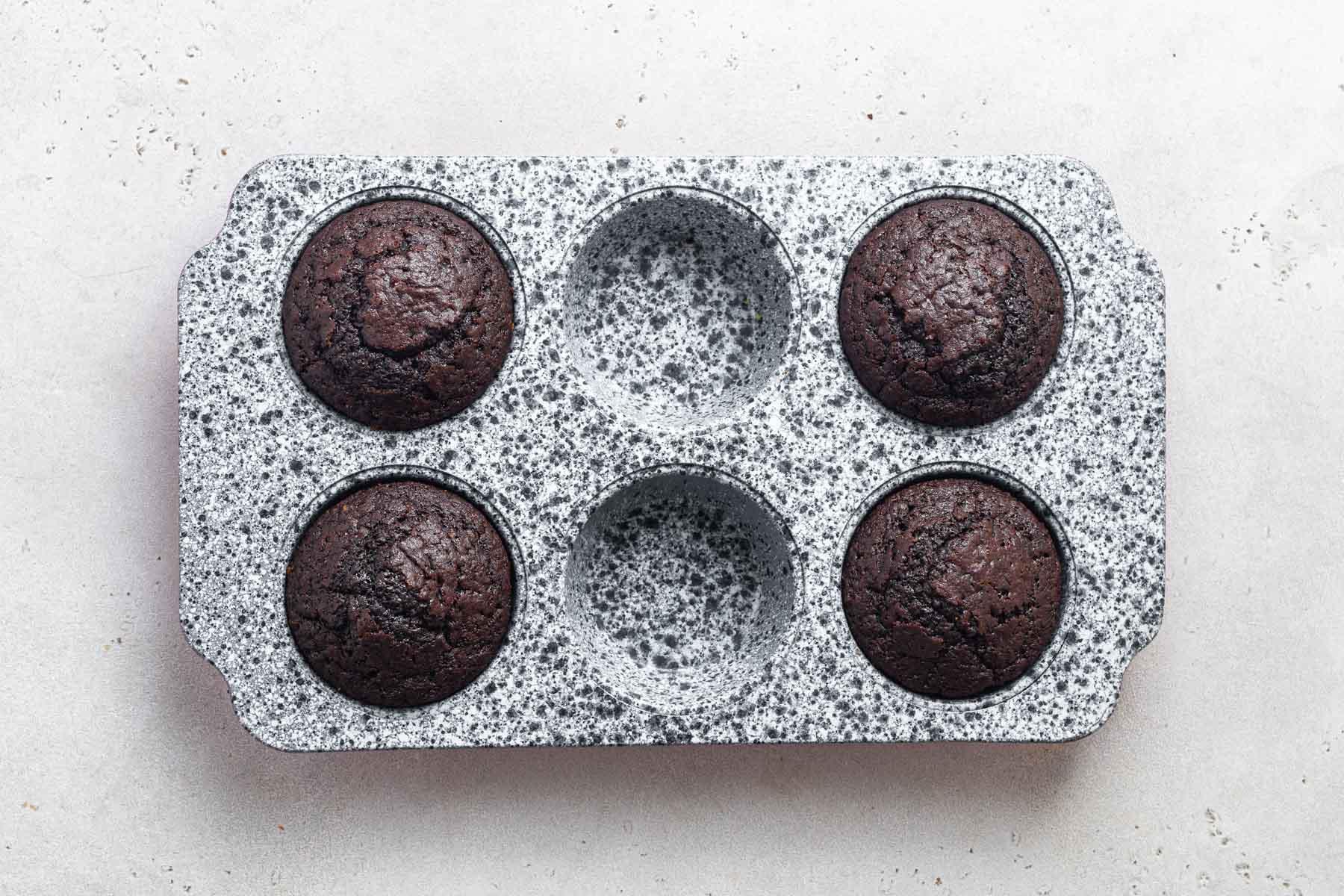 Freshly baked chocolate cupcakes in pan.