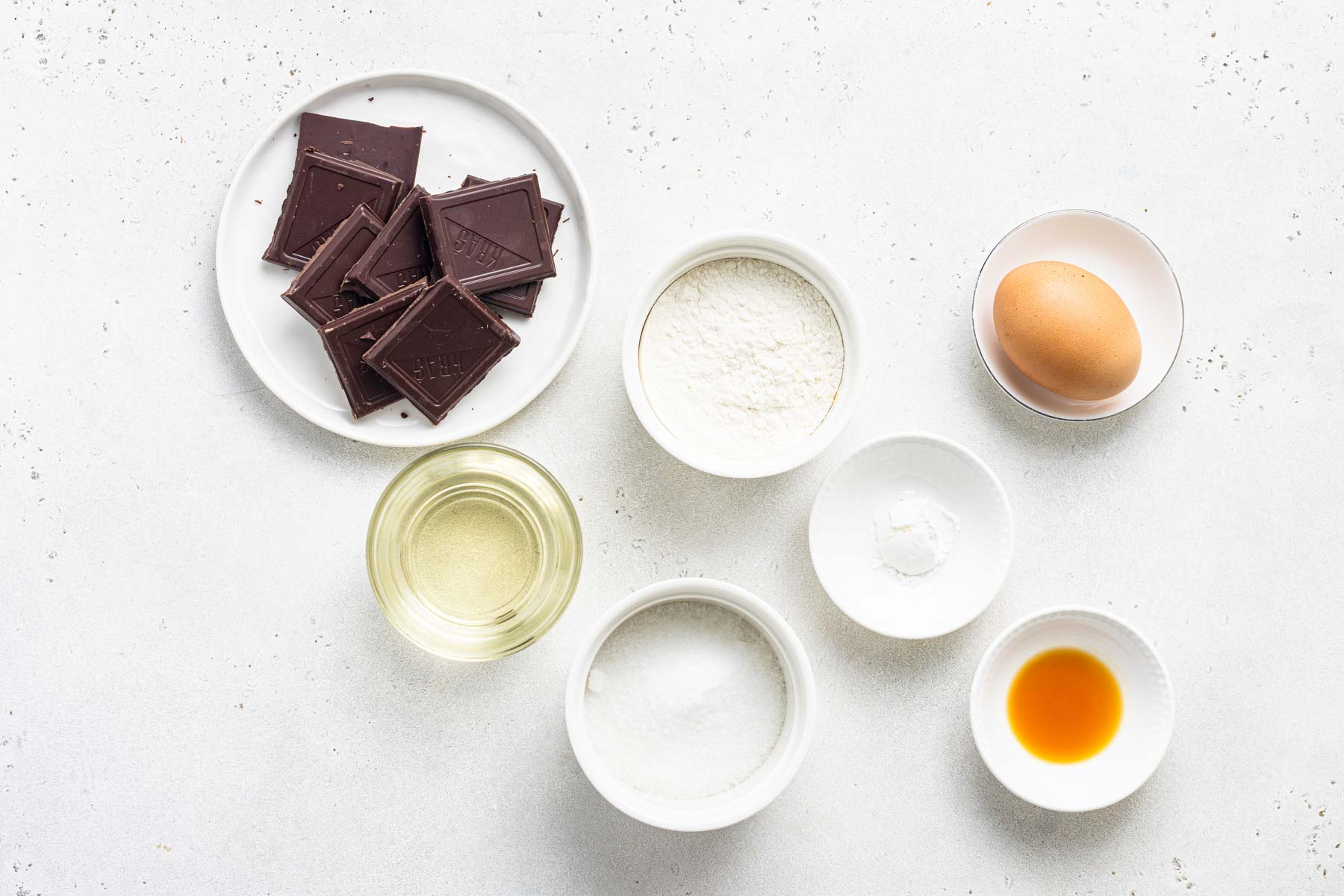 Ingredients to make a small batch of chocolate cupcakes on white table.