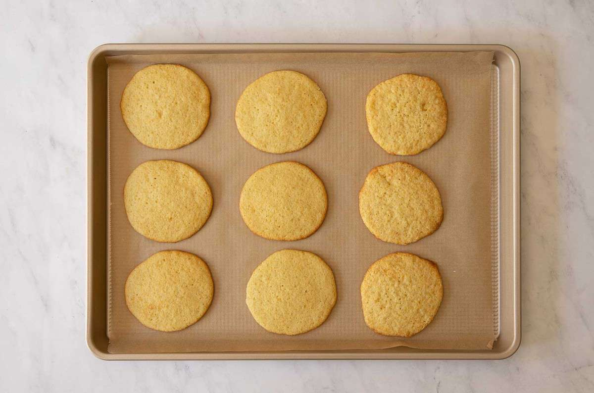 Nine baked cookies on a baking sheet.