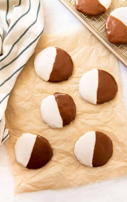 Five black and white striped cookies on parchment paper.