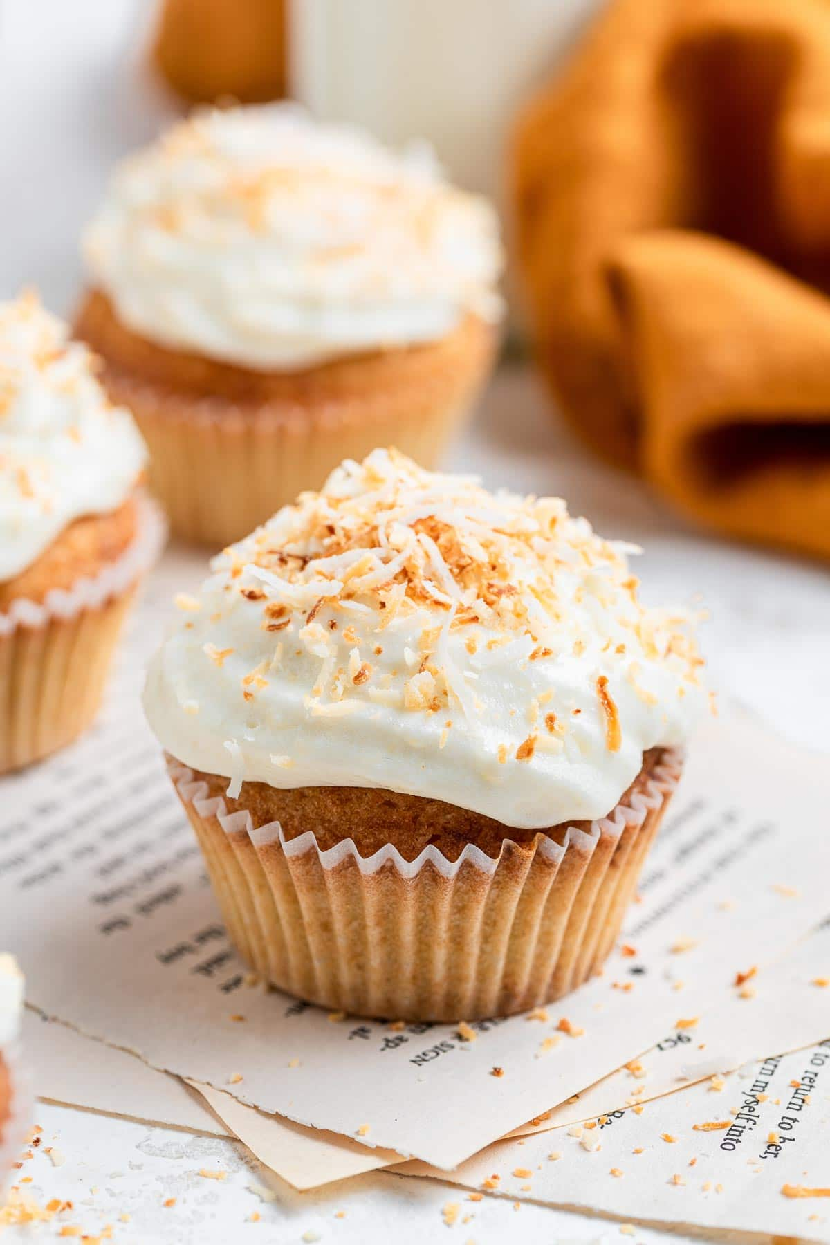 Up close of coconut cupcake decorated with coconut flakes.