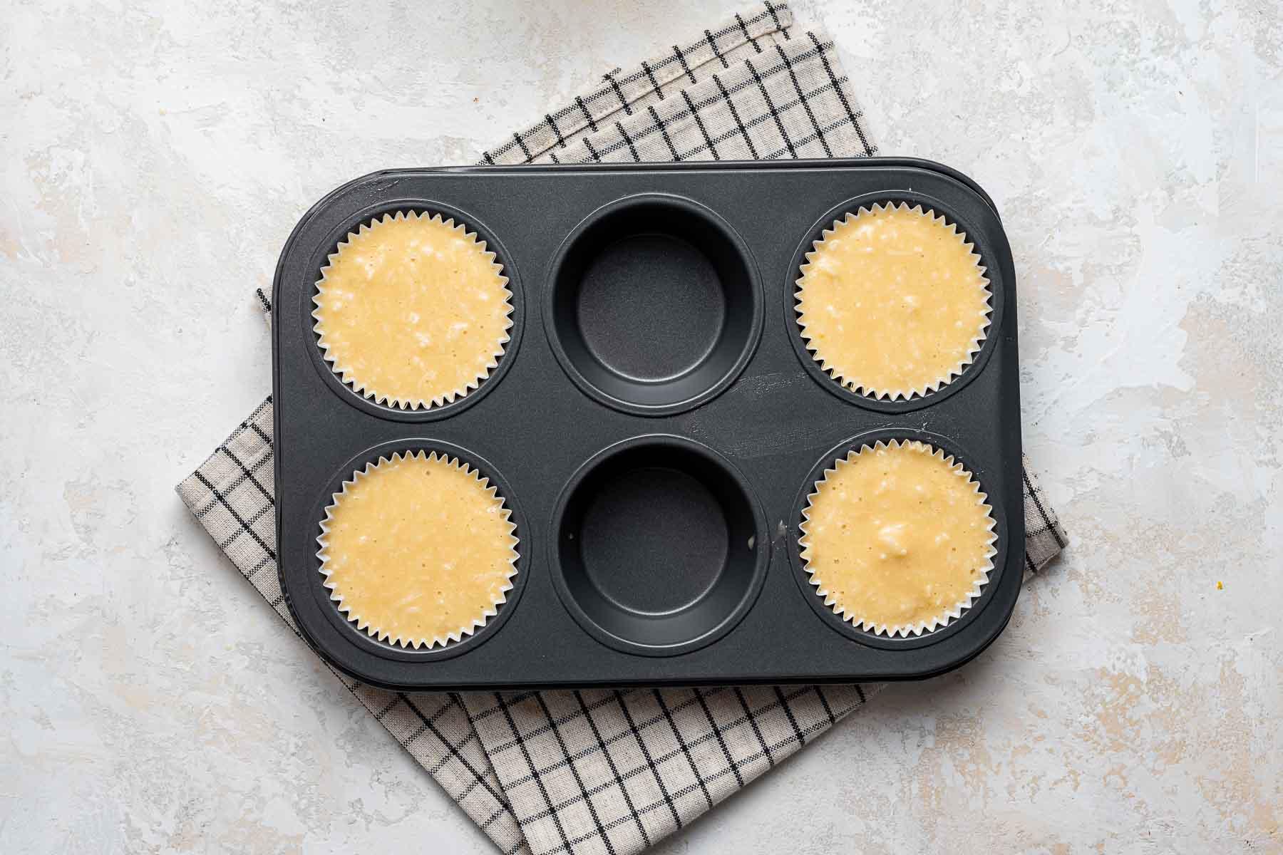 Raw coconut cupcake batter in muffin pan.
