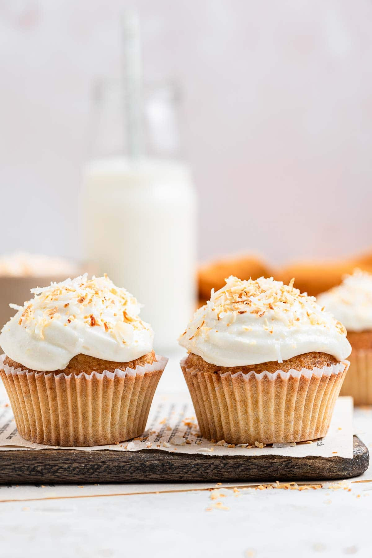 Two frosted coconut cupcakes with milk in the background.