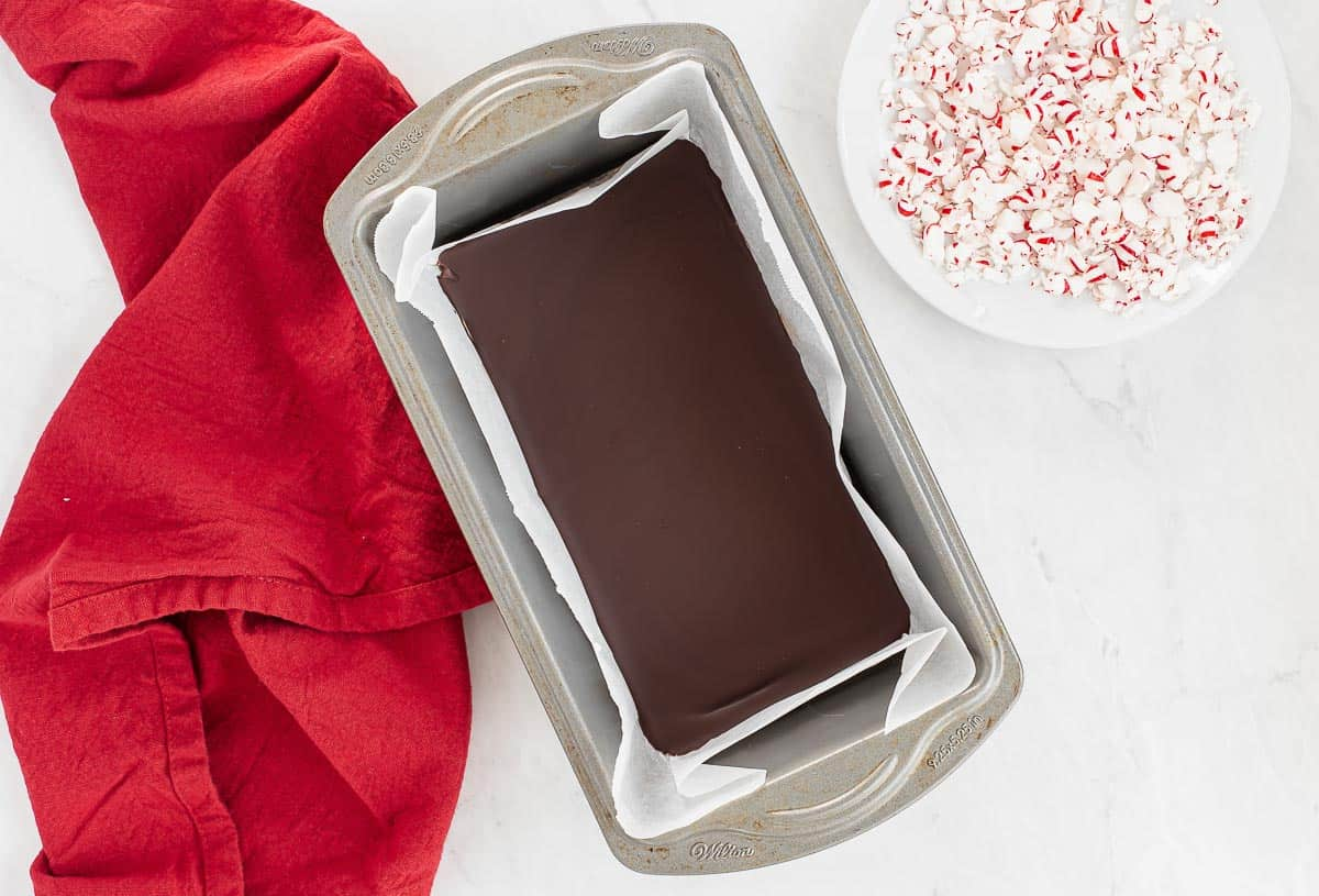 set chocolate in a loaf pan with crushed peppermints on the side