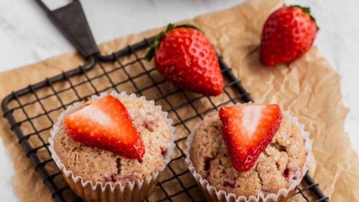 Strawberry Muffins on a wire rack with fresh strawberry slices on top.