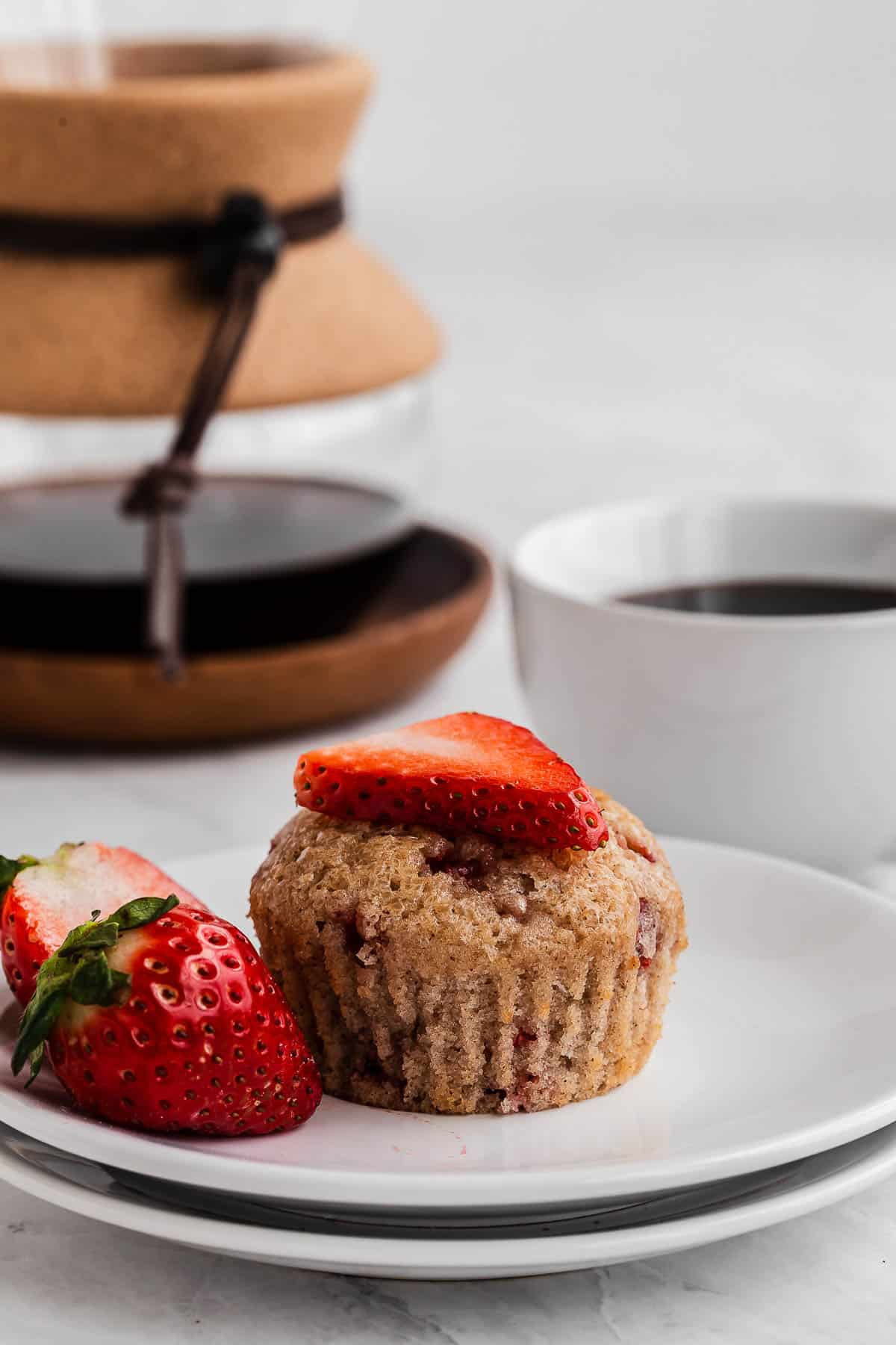 Strawberry muffin on a plate with coffee cup.