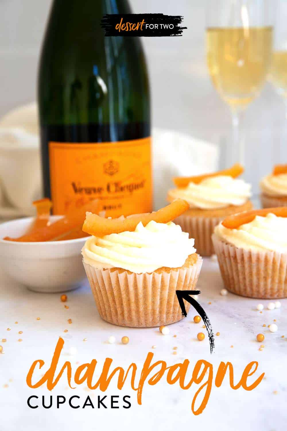 Close up of champagne cupcakes with sprinkles and champagne bottle in background.