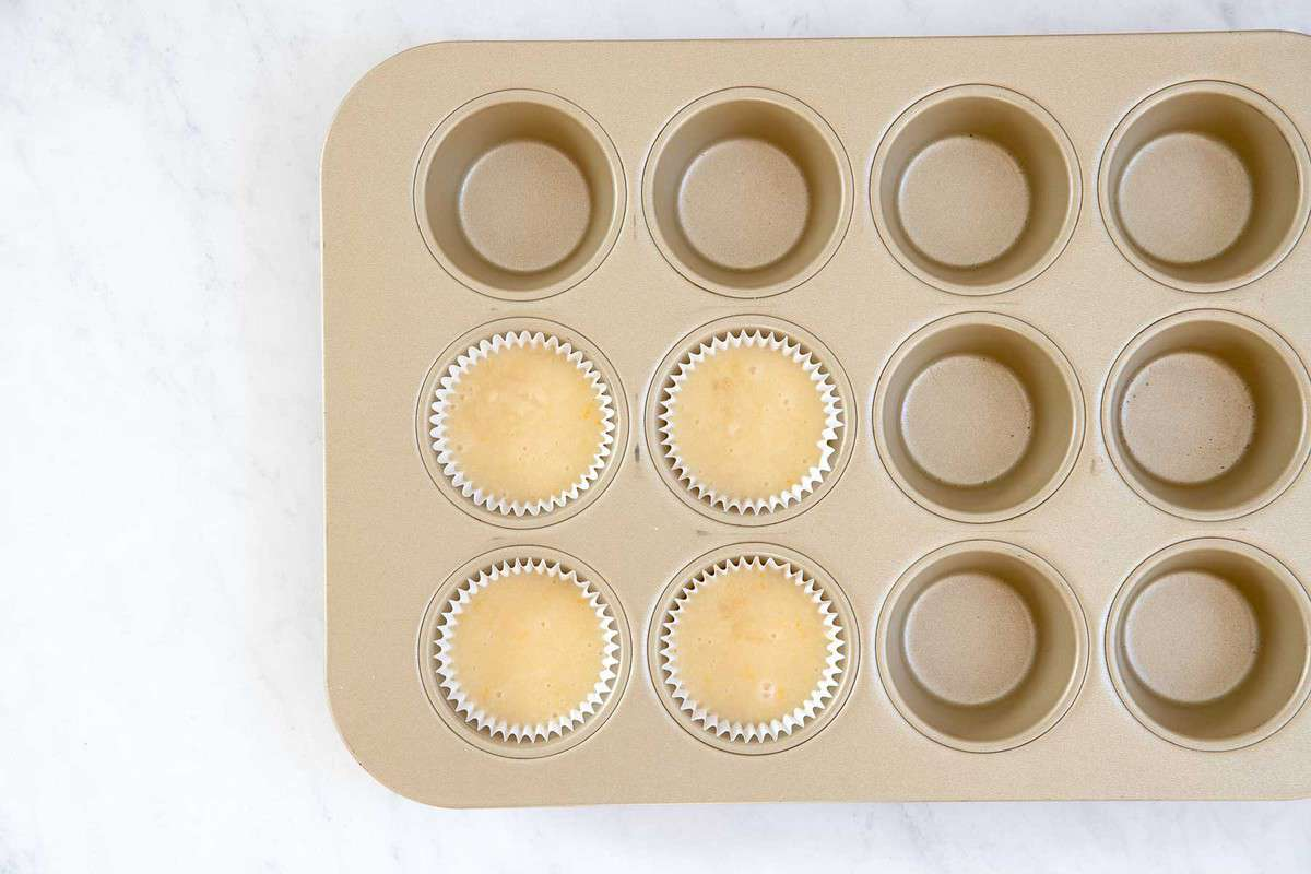 Batter for four cupcakes in a muffin pan.