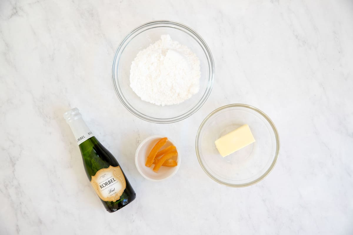 Ingredients for champagne buttercream frosting in small bowls.