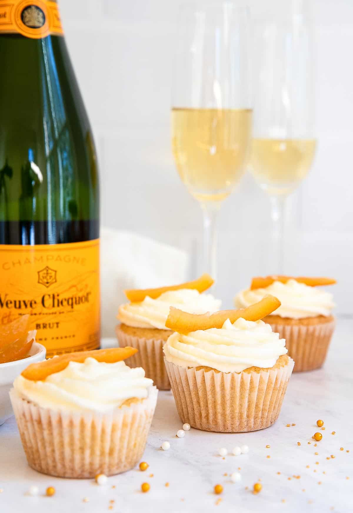Champagne cupcakes with orange zest on top and bottle of champagne.