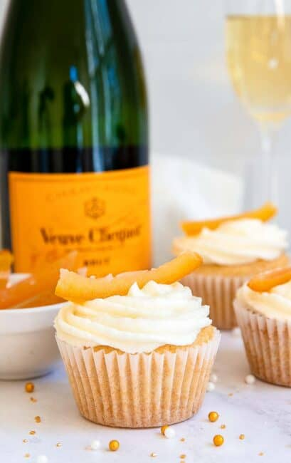 White cupcakes with champagne bottle in background.