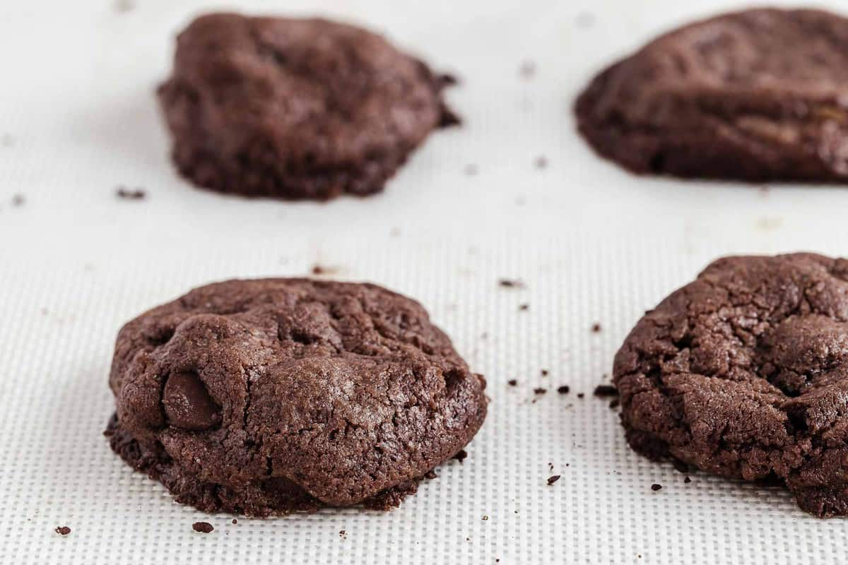 Chocolate cookies on white silicone mat cookie sheet.