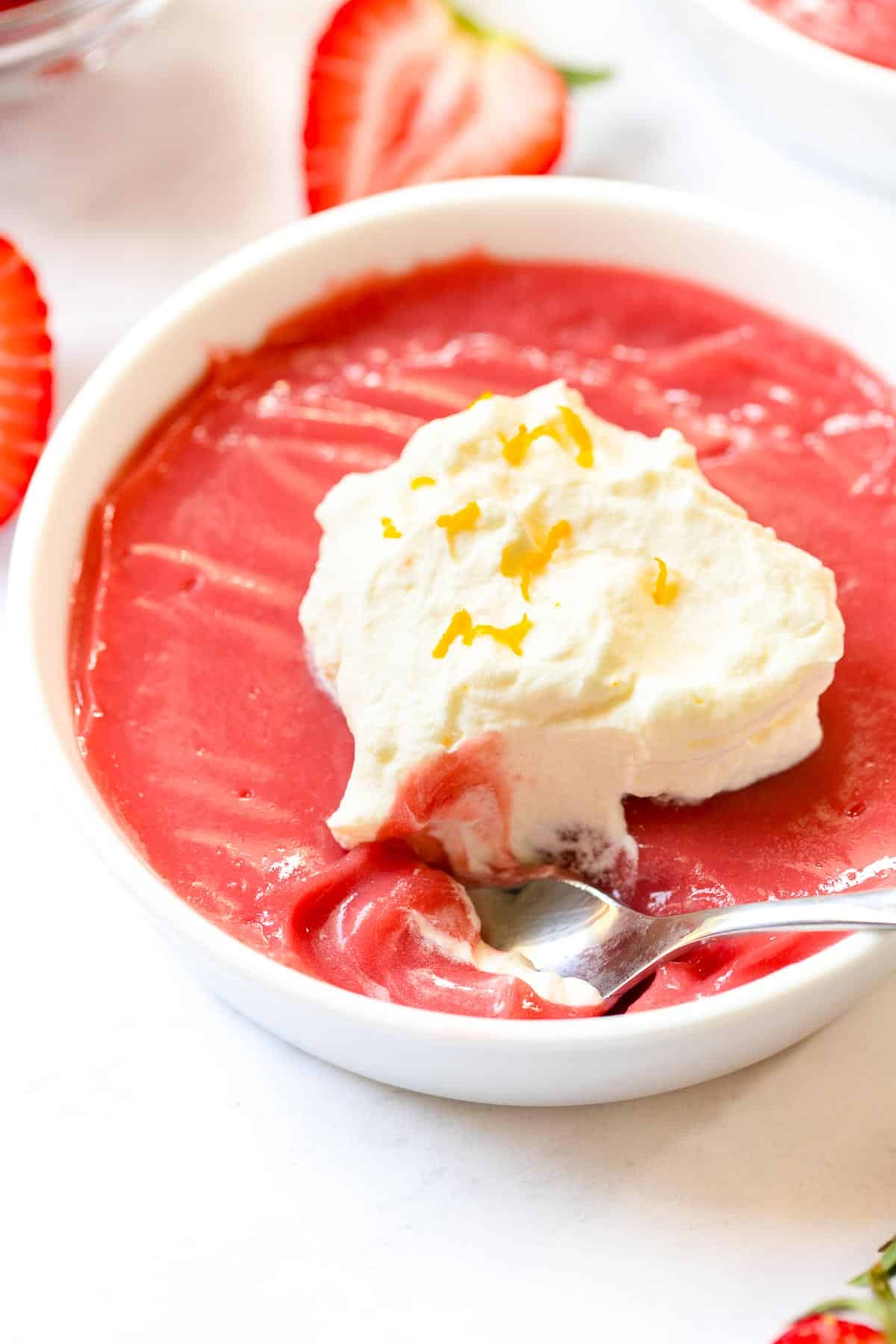 Bowl of strawberry pudding with bite missing.