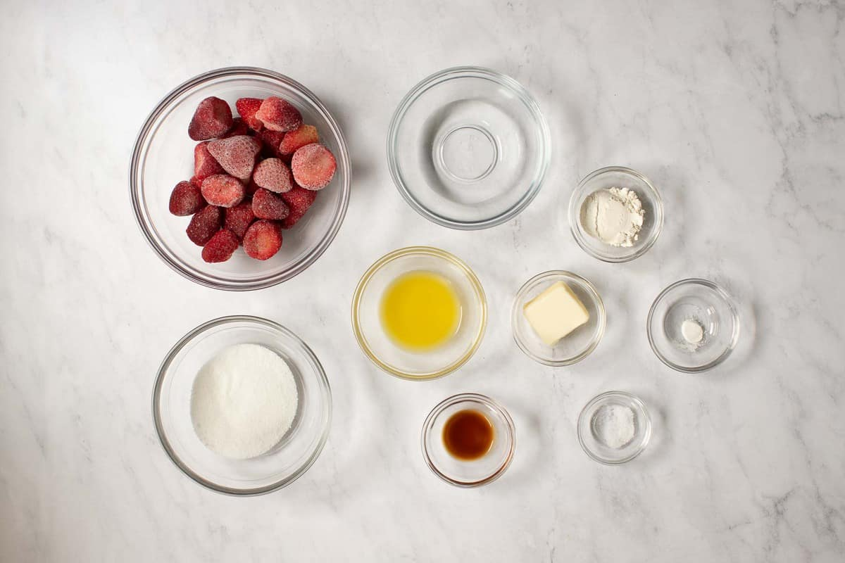 Ingredients in small bowls on marble table.