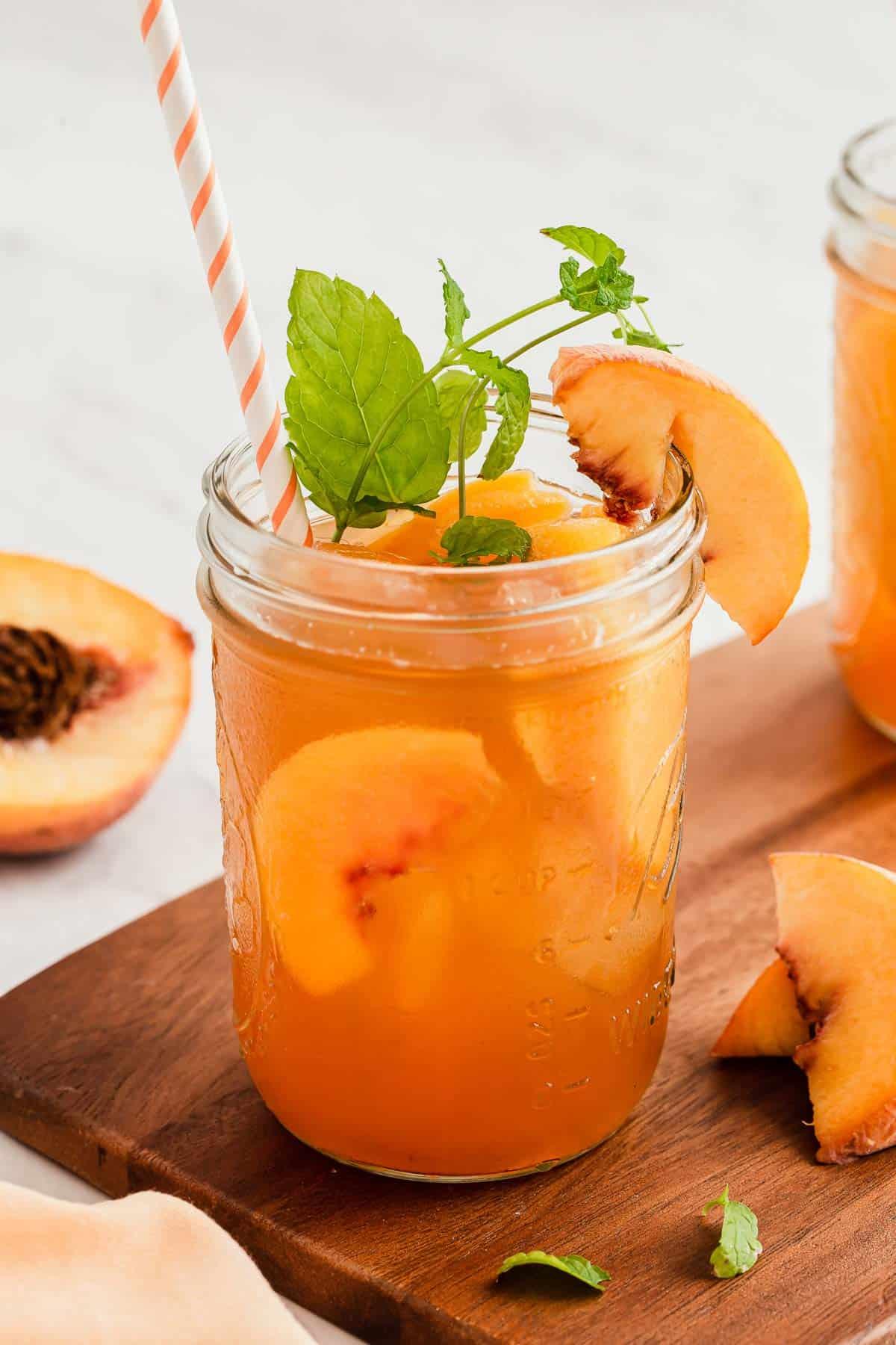 Mason jar of peach iced tea with fresh mint sprig.