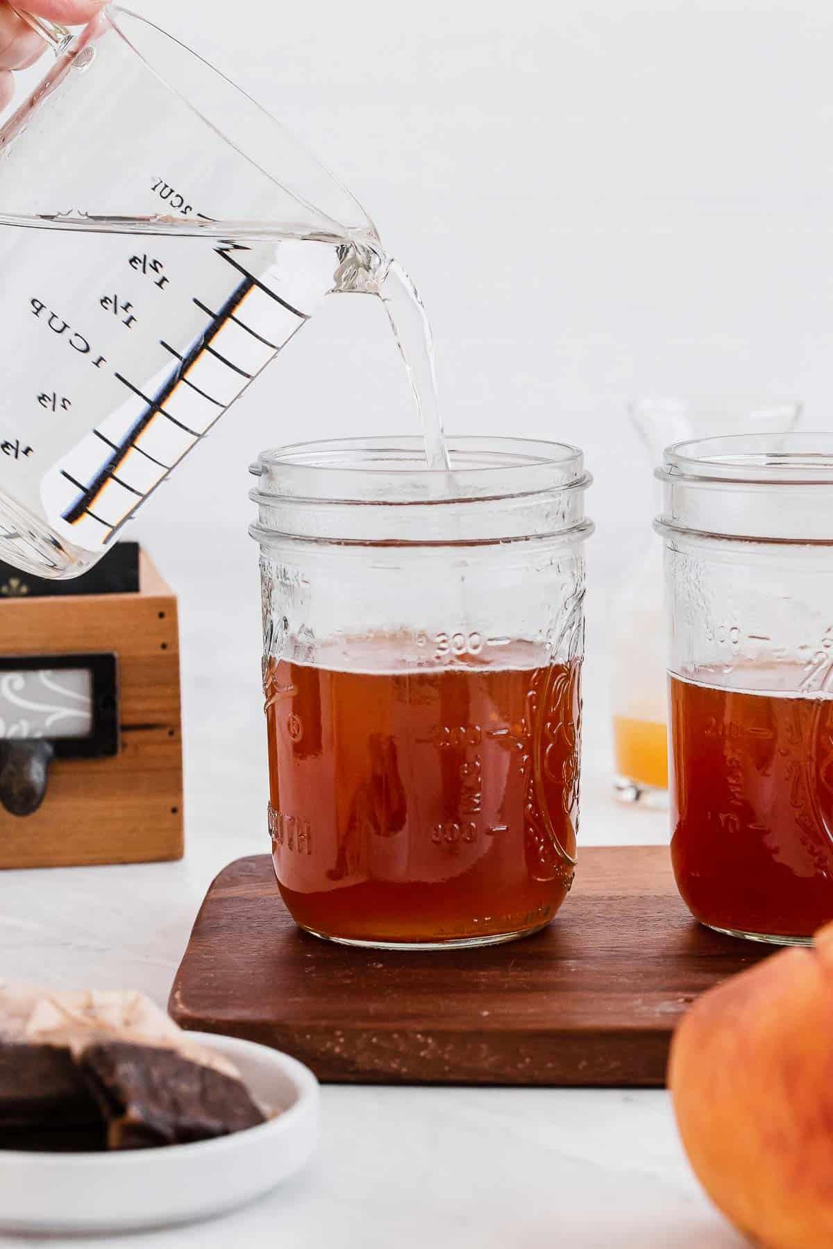 Adding cool water to peach iced tea in mason jars.