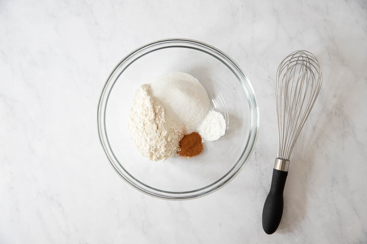 Clear bowl with flour, baking powder, nutmeg, and salt and a whisk on the side.