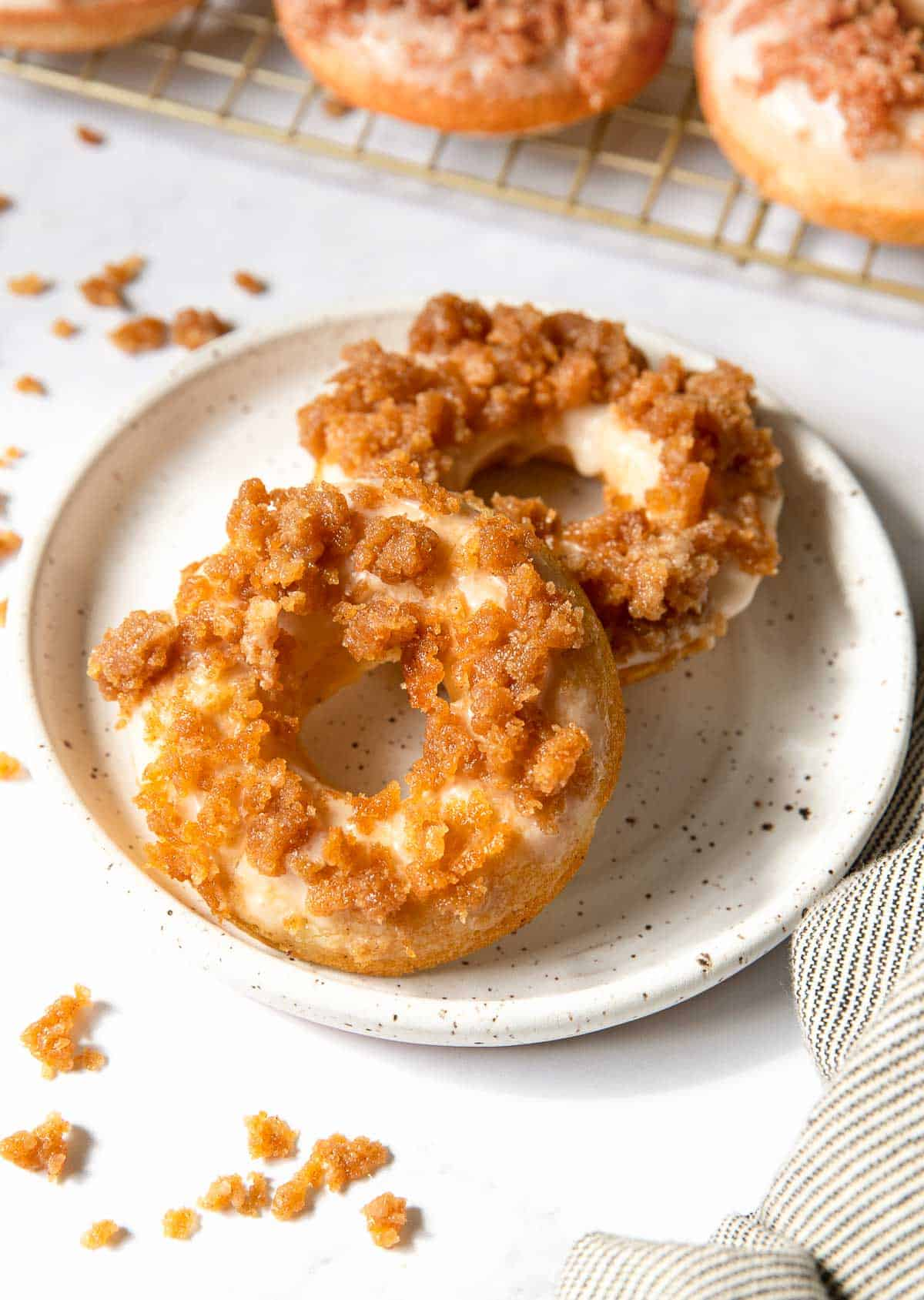 Two streusel topped donuts on a plate.