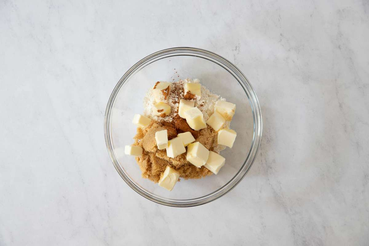 Clear bowl with butter cubes and brown sugar.
