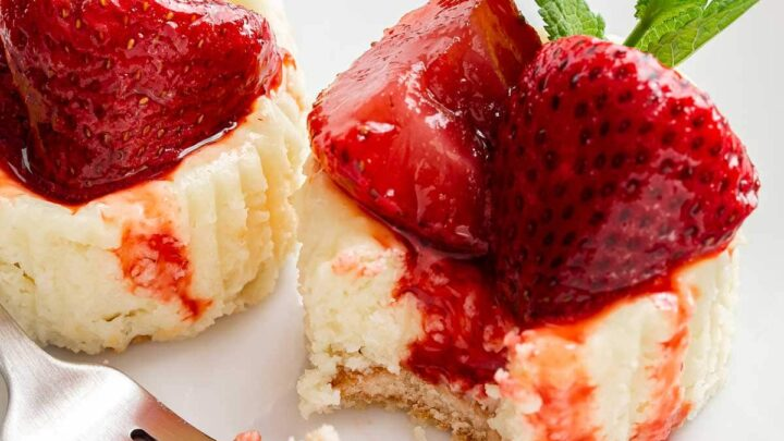 Two mini strawberry cheesecakes on a plate with a fork.