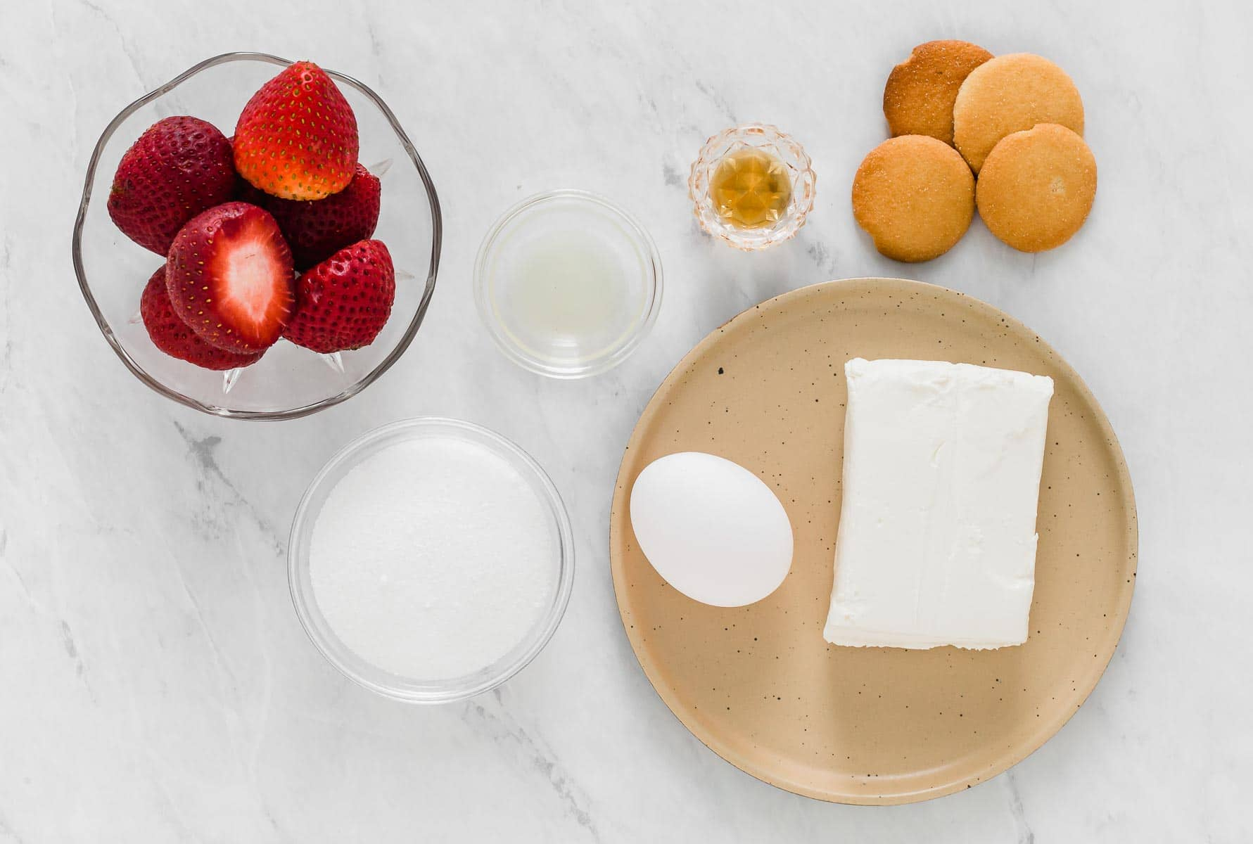 Ingredients for mini cheesecakes on a white table.