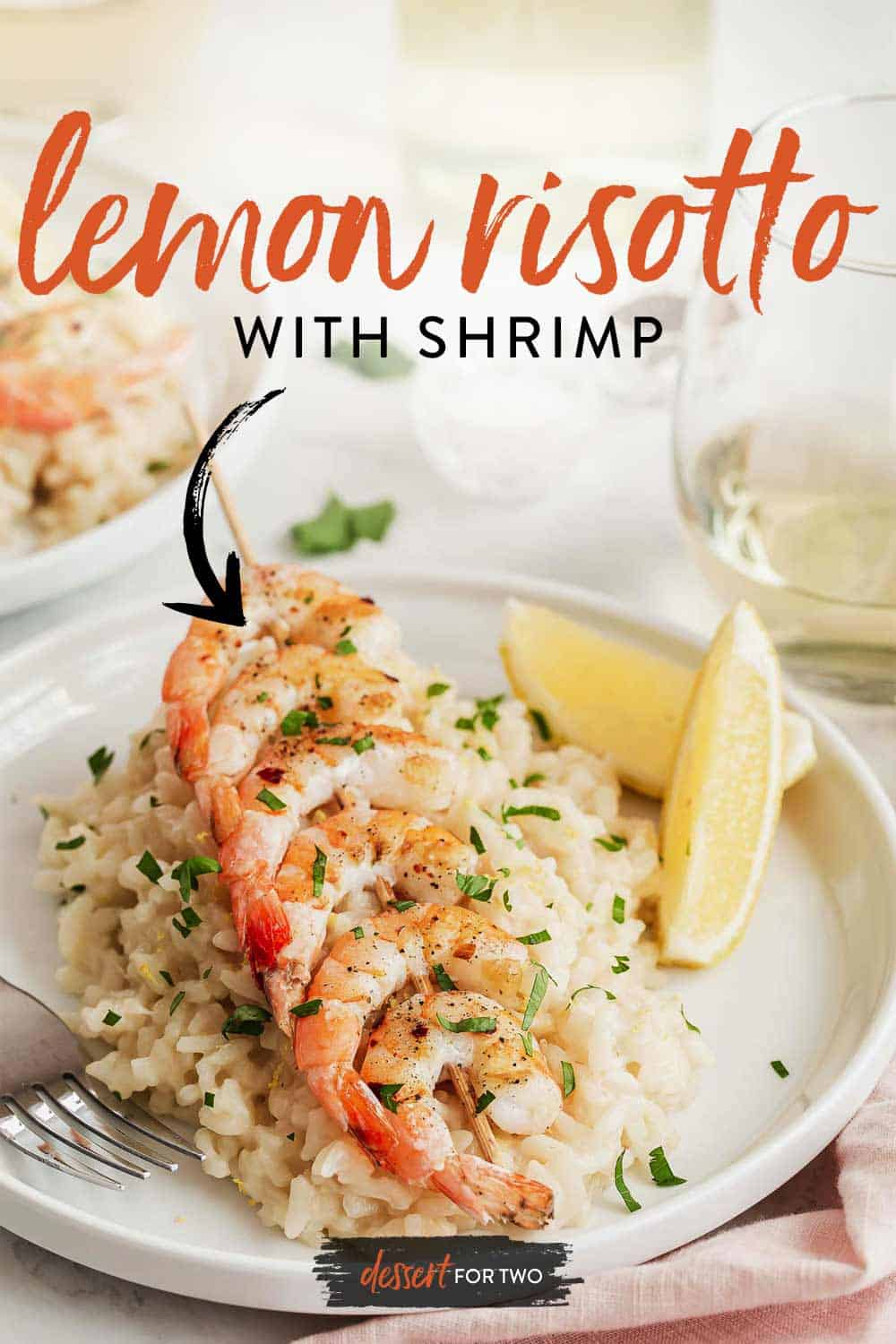 Plate of shrimp on top of creamy rice with lemon wedges and white wine.