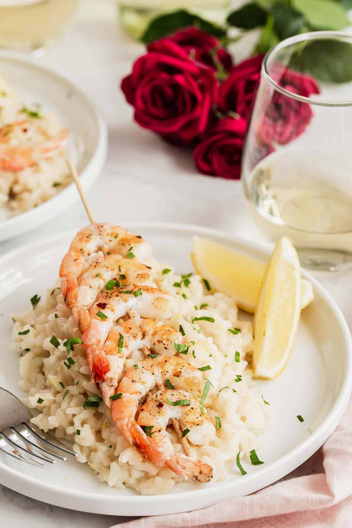 Two plate of lemon risotto with grilled shrimp on top