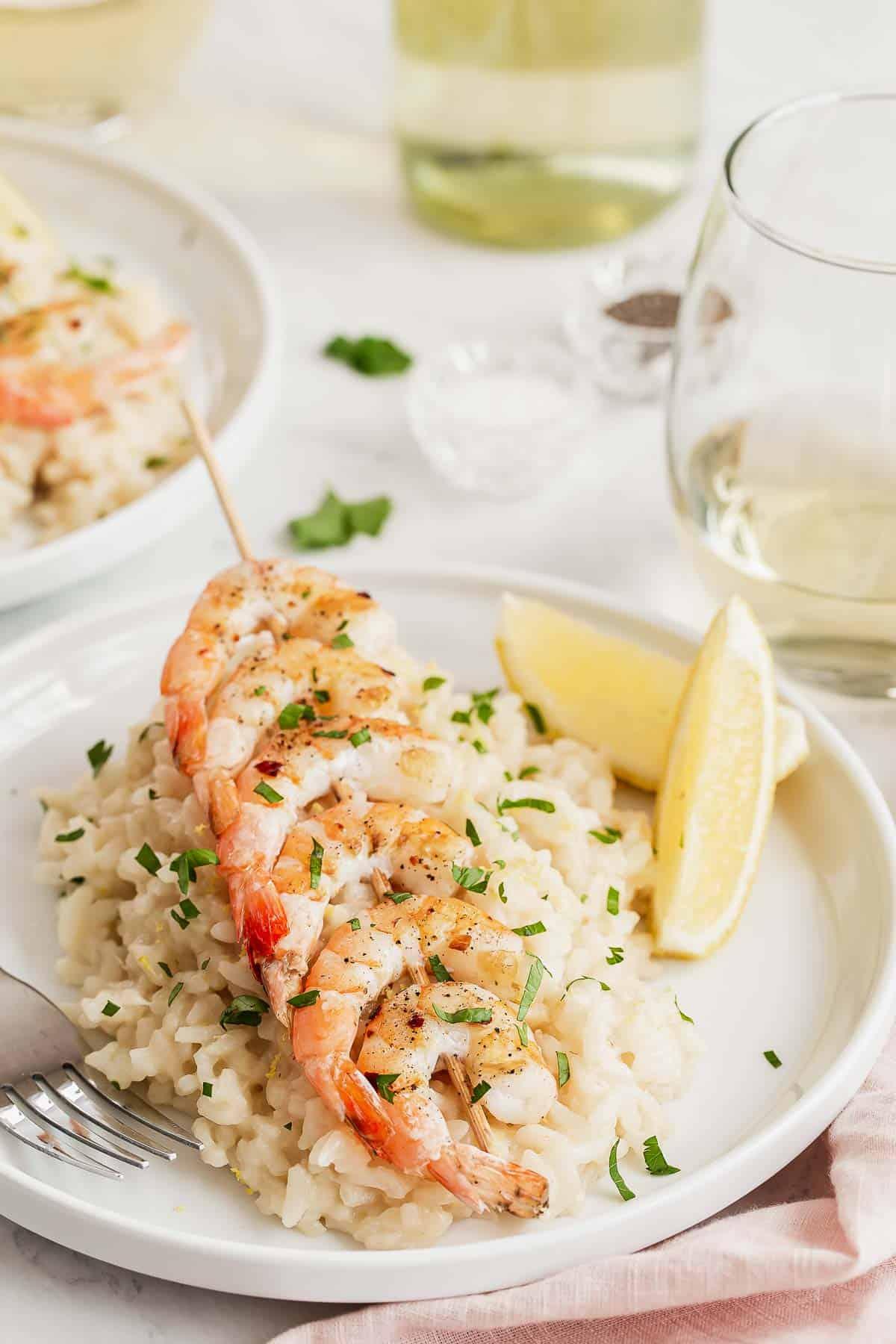 Shrimp on a skewer over risotto with lemon wedges.