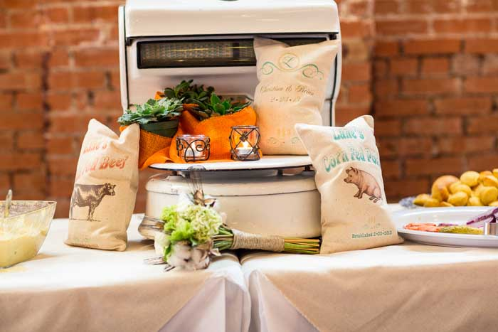 Another theme of the decor was vintage scales. Since our reception was in a flour mill, we mimicked the large ground scales found throughout the building. My wedding planner made us personalized flour sack towels that said 'Lane Grass Fed Beef' and 'Lane Corn Fed Pork.' I was so surprised! The orange burlap with the succulents was a nice touch by the florist. I didn't notice it until the photos, honestly! The bouquet in front made of wheat and cotton is from my maid of honor.