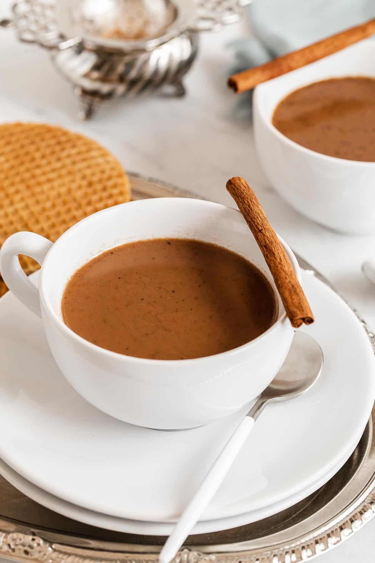 White mug of chai latte with cinnamon stick on edge.