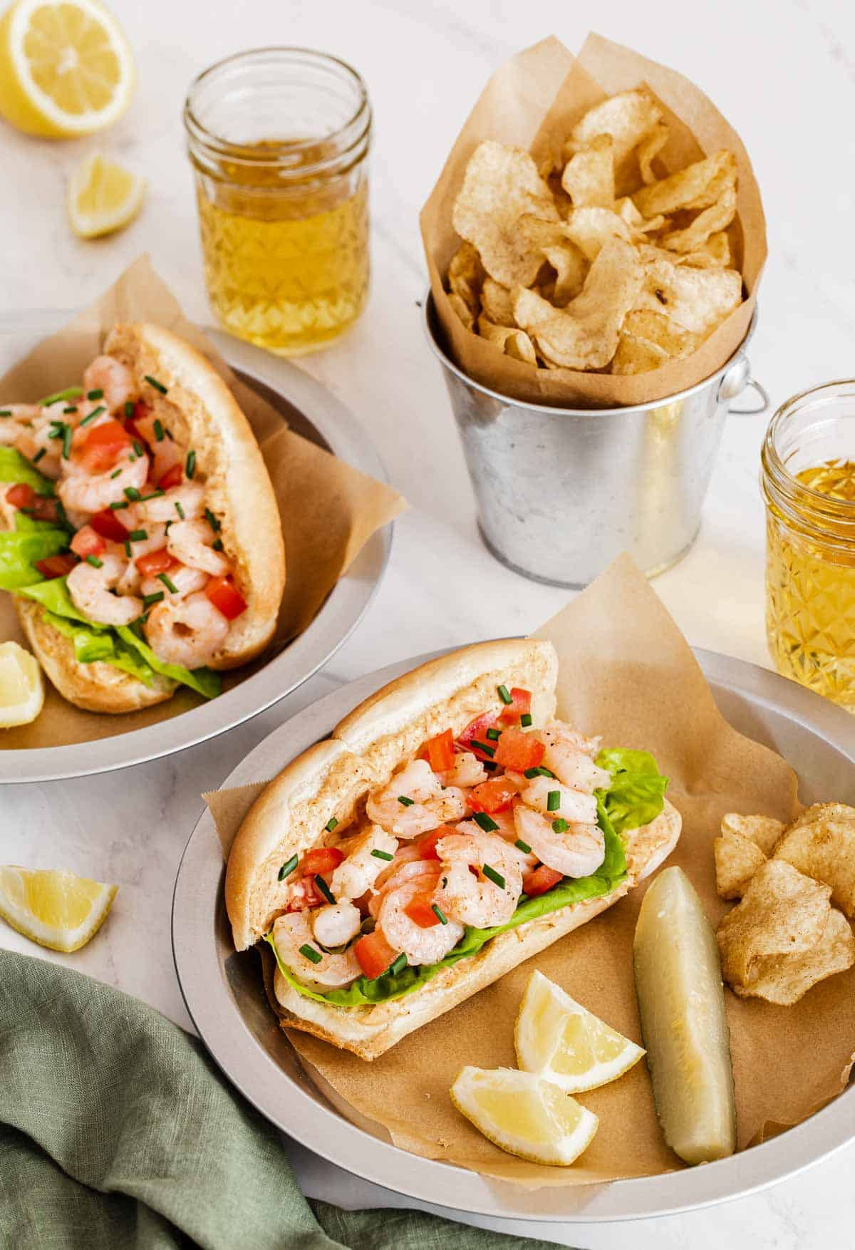 Shrimp Po Boys on plates with chips and pickles.