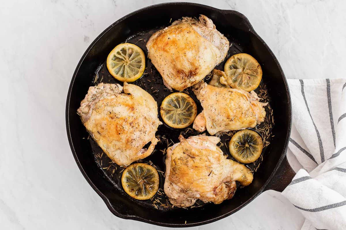 chicken thighs in a cast iron skillet with lemon slices and rosemary