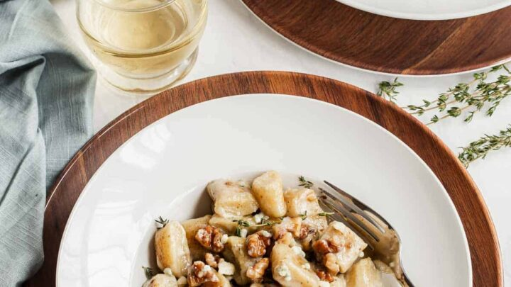 Two serving plates of ricotta gnocchi with white wine on the side.