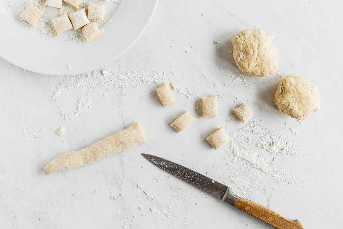 Raw gnocchi dough being rolled and cut into shapes.