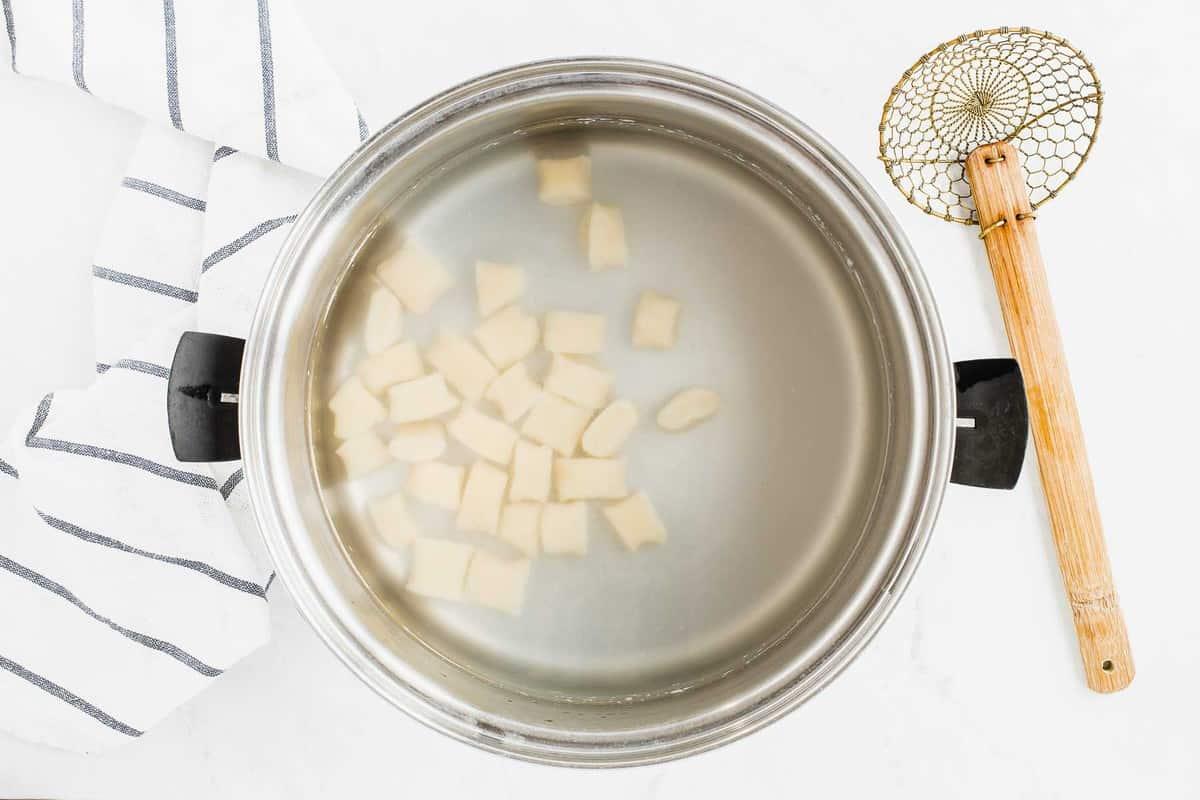 Ricotta gnocchi boiling in stock pot.