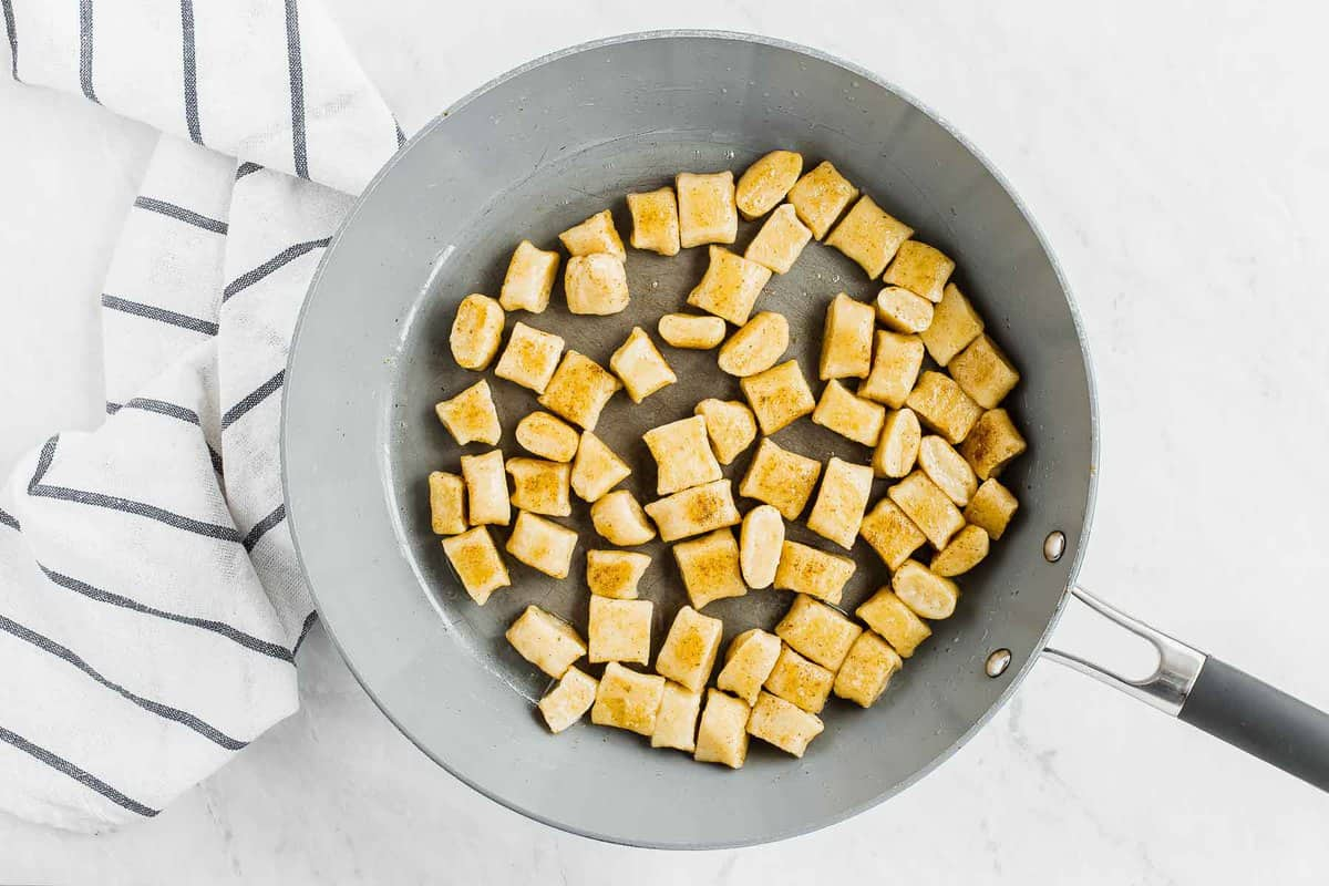 Cooked gnocchi, tossing in butter in skillet.
