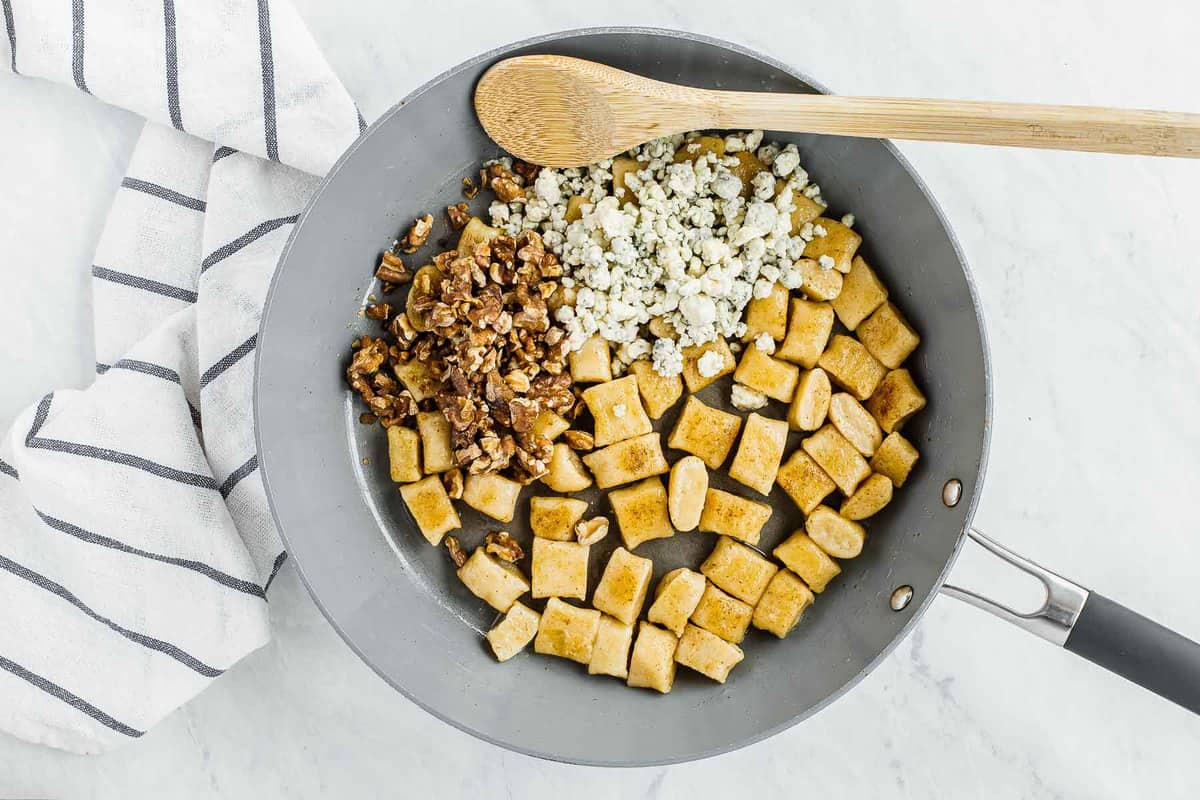 Gnocchi in skillet with walnuts and blue cheese crumbles.