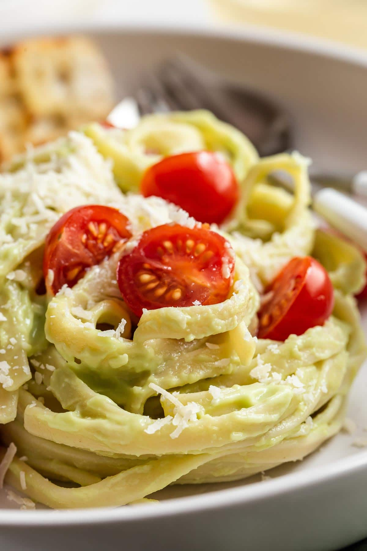 Avocado sauce on noodles with cherry tomatoes.