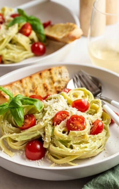 Avocado pasta with tomatoes and grilled bread on plates.