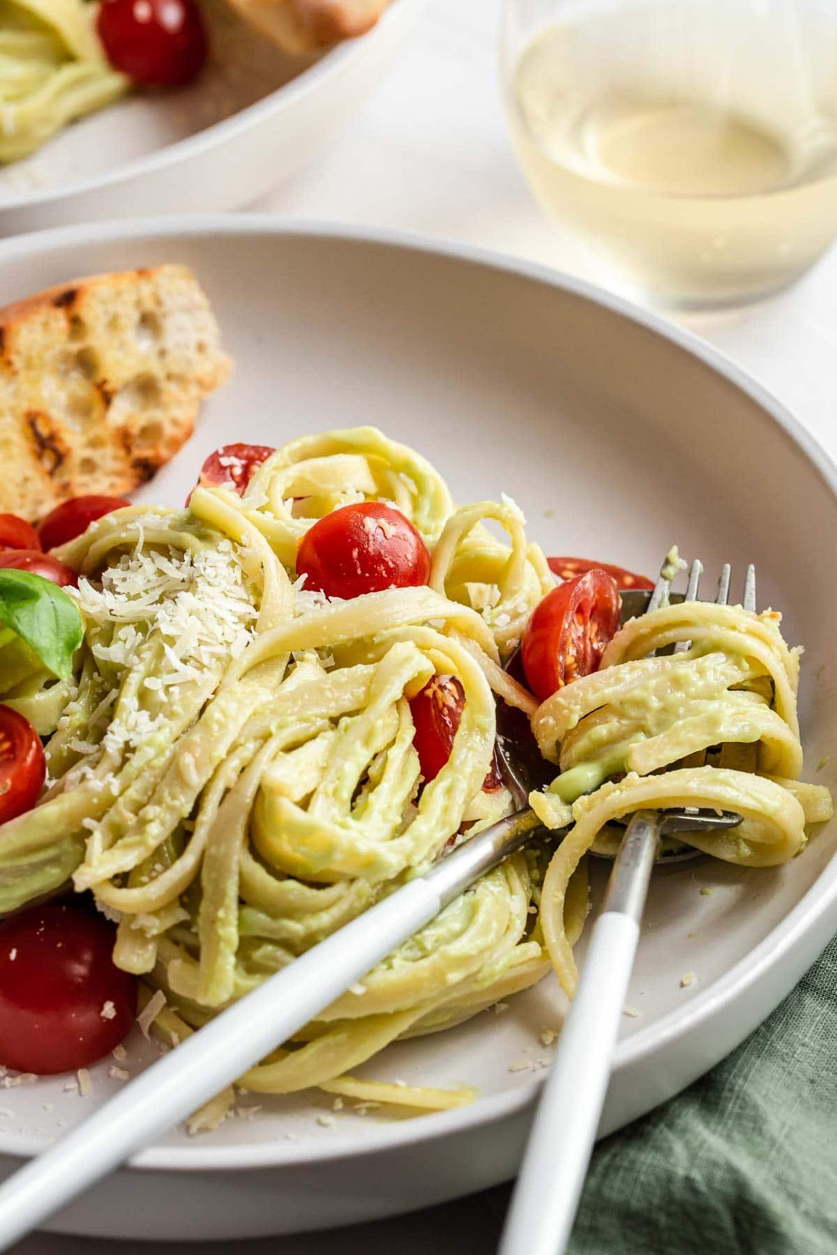 Fork in pasta noodles on plate.